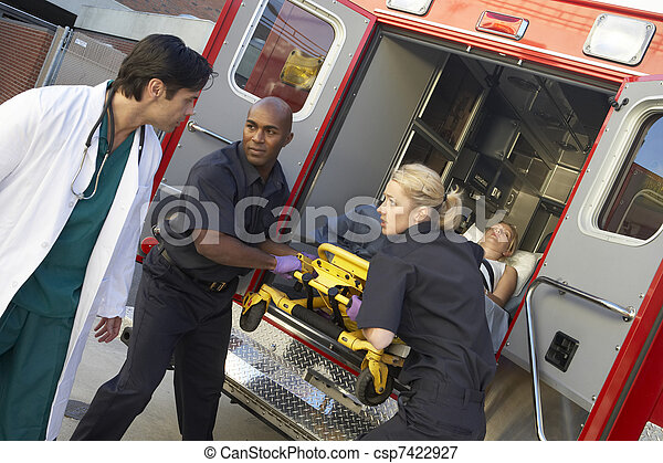 Paramedics and doctor unloading patient from ambulance - csp7422927