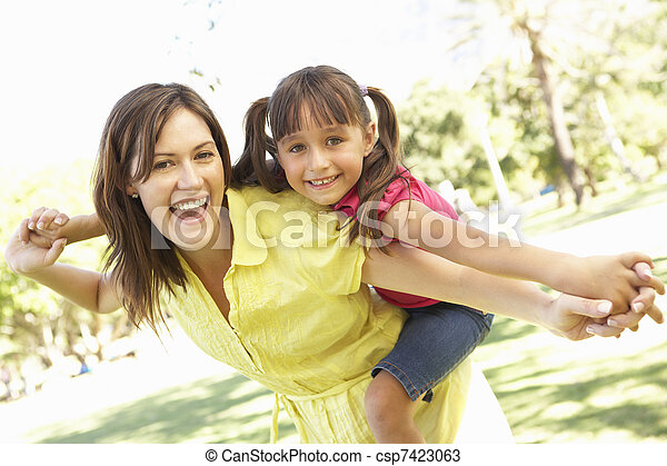 Mother Giving Daughter Ride On Back In Park - csp7423063