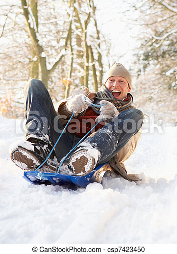 Man Sledging Through Snowy Woodland - csp7423450