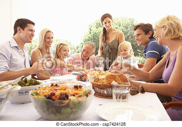 A family, with parents, children and grandparents, enjoy a picnic - csp7424128