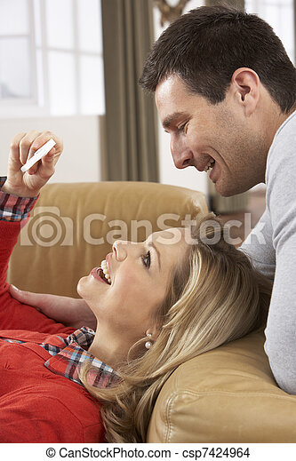 Couple Looking At Result Of Home Pregnancy Test Kit - csp7424964