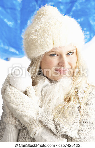 Young Woman Wearing Warm Winter Clothes And Fur Hat Holding Snowball In Studio - csp7425122
