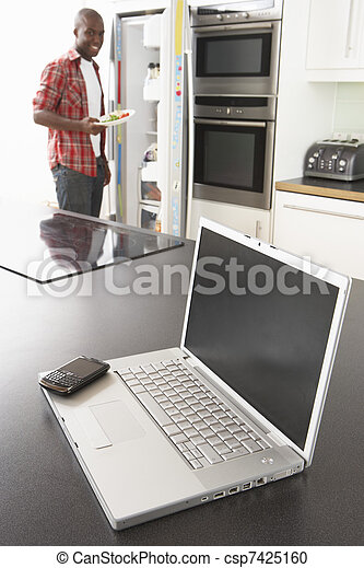 Young Man Fixing Snack In Kitchen With Laptop In Modern Kitchen - csp7425160