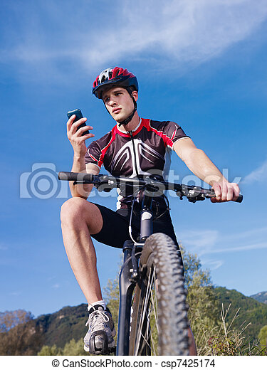 young man with telephone riding mountain bike  - csp7425174