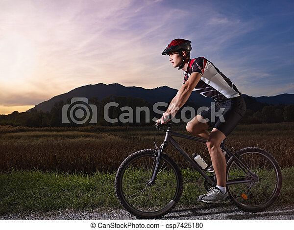 young man training on mountain bike at sunset - csp7425180