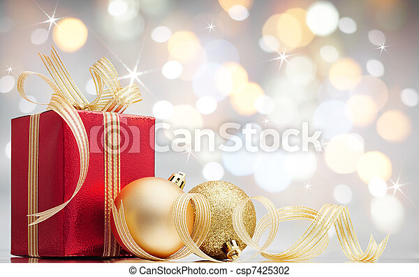 Stock Photo of christmas present - christmas gift and baubles against bokeh...