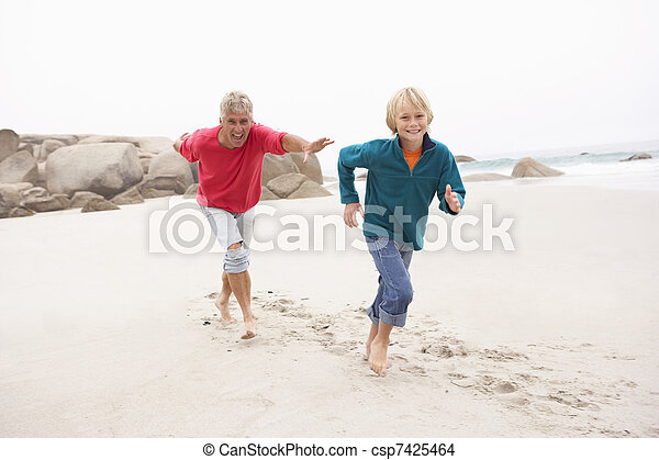 Grandfather Chasing Grandson Along Winter Beach - csp7425464