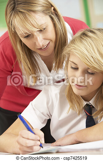 Female Teenage Student Studying In Classroom With Teacher - csp7425519