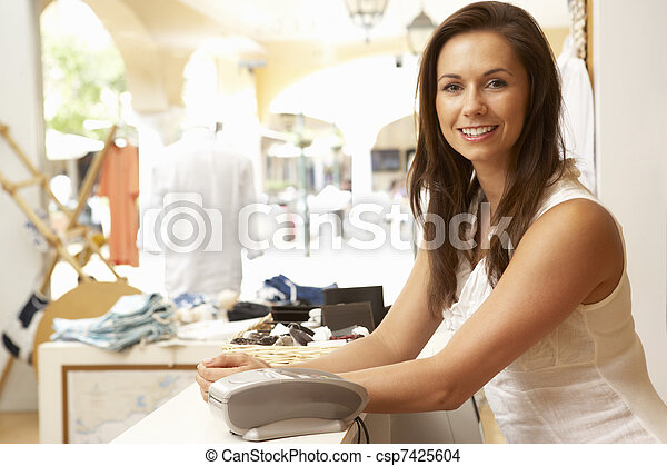 Female Sales Assistant At Checkout Of Clothing Store - csp7425604