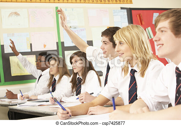 Teenage Student Answering Question Studying In Classroom - csp7425877