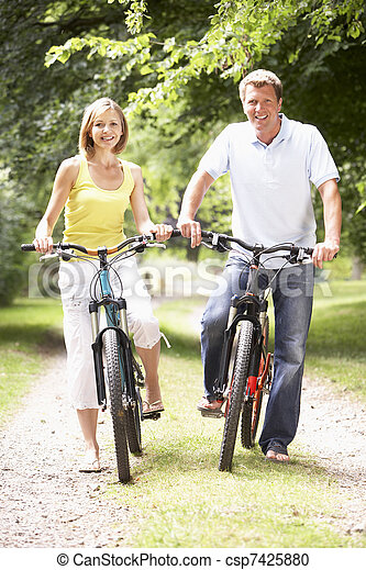 Couple riding bikes in countryside - csp7425880