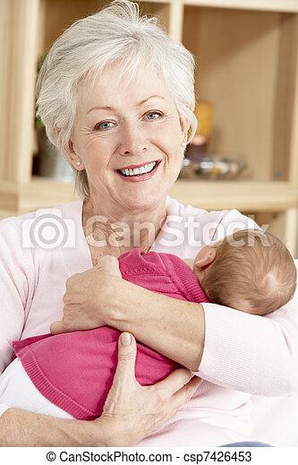 Grandmother Cuddling Granddaughter At Home - csp7426453