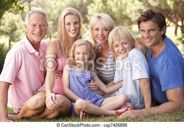 A family, with parents, children and grandparents, relaxing in a park - csp7426899