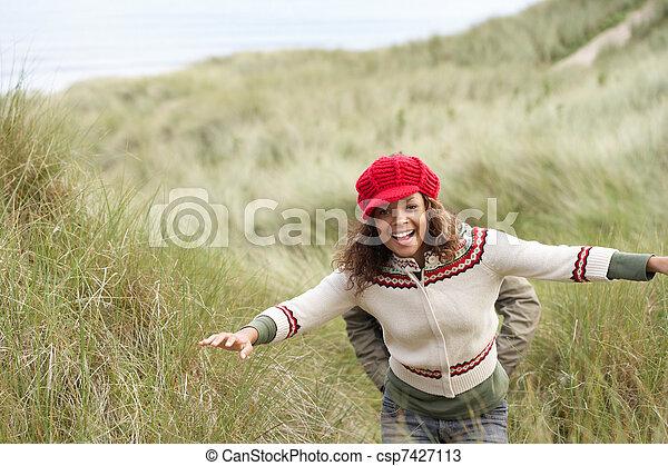 Teenage Girl Walking Through Sand Dunes Wearing Warm Clothing - csp7427113