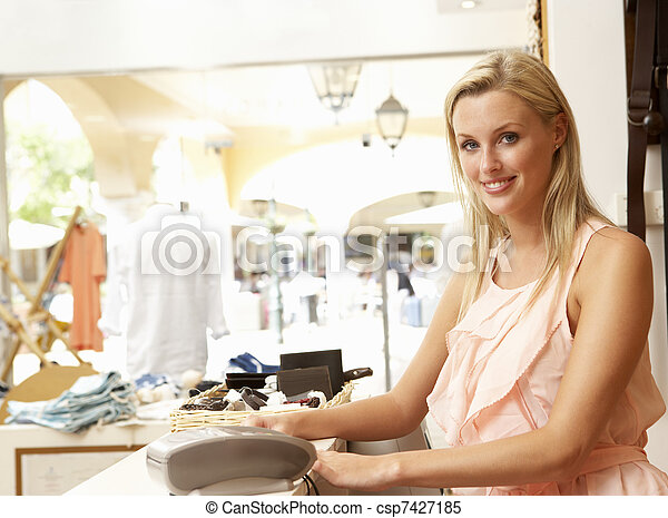 Female Sales Assistant At Checkout Of Clothing Store - csp7427185