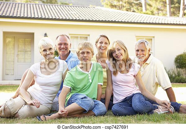 Extended Family Sitting Outside Dream Home