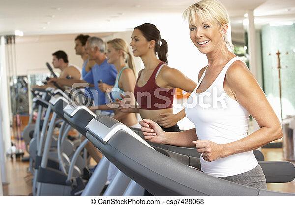 Senior Woman On Running Machine In Gym - csp7428068
