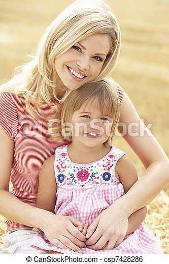 Mother And Daughter Sitting On Straw Bales In Harvested Field - csp7428286
