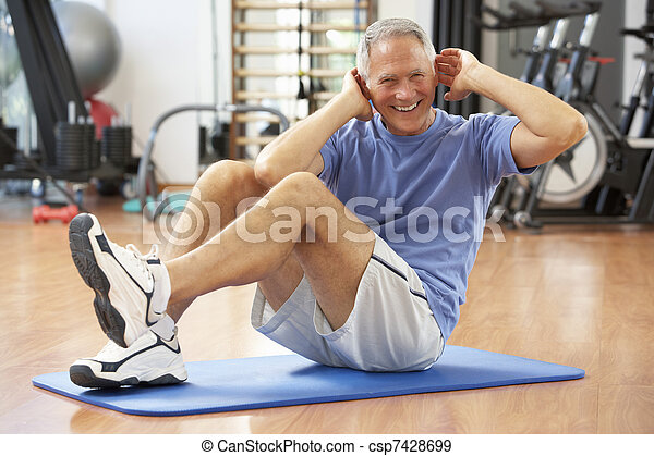 Senior Man Doing Sit Ups In Gym - csp7428699
