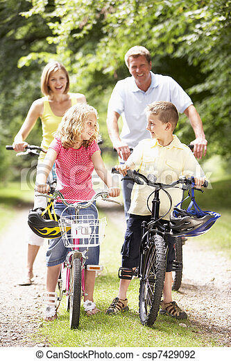 Family riding bikes in countryside - csp7429092
