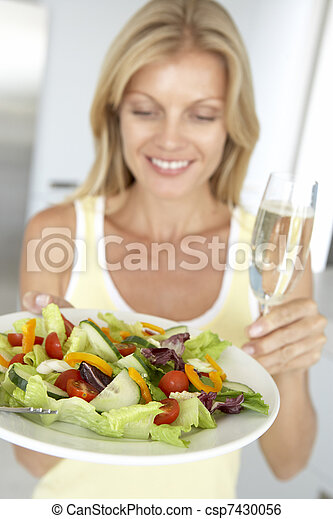 Mid Adult Woman Holding A Wine Glass And Fresh Salad - csp7430056