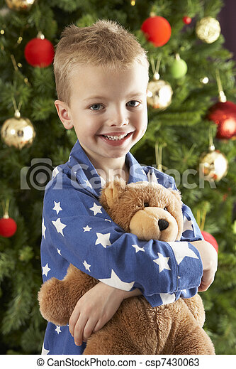Young Boy Cuddling Teddy Bear In Front Of Christmas Tree - csp7430063