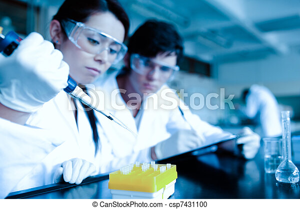Cute scientist dropping liquid in test tubes while her partner is taking notes in a laboratory - csp7431100