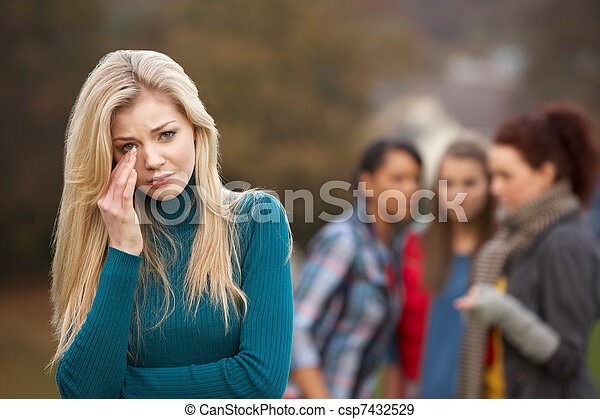 Upset Teenage Girl With Friends Gossiping In Background - csp7432529
