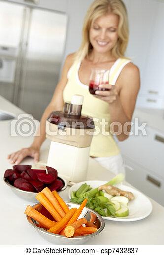 Mid Adult Woman Making Fresh Vegetable Juice - csp7432837