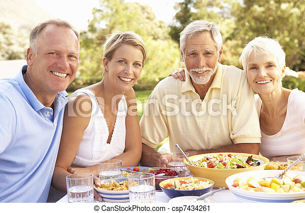 Adult Son And Daughter Enjoying Meal In Garden With Senior Parents - csp7434261