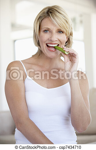 Mid Adult Woman Smiling At Camera And Eating Celery Stick - csp7434710