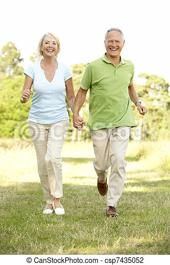 Mature couple walking in countryside - csp7435052