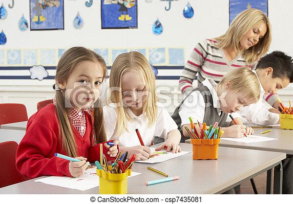 Group Of Primary Schoolchildren And Teacher Having lesson In Classroom - csp7435081