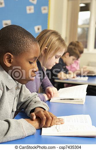 Schoolboy Reading Book In Classroom - csp7435304