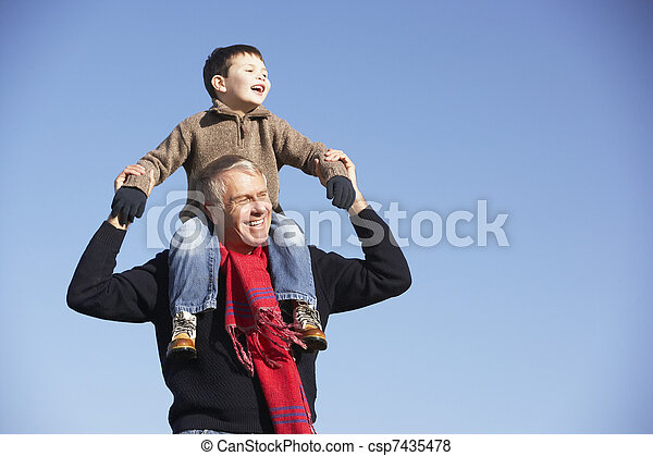 Grandfather Carrying Grandson On His Shoulders - csp7435478
