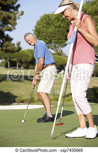 Senior Couple Golfing On Golf Course Lining Up Putt On Green - csp7435669
