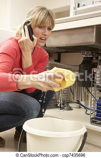Woman Mopping Up Leaking Sink On Phone To Plumber - csp7435696