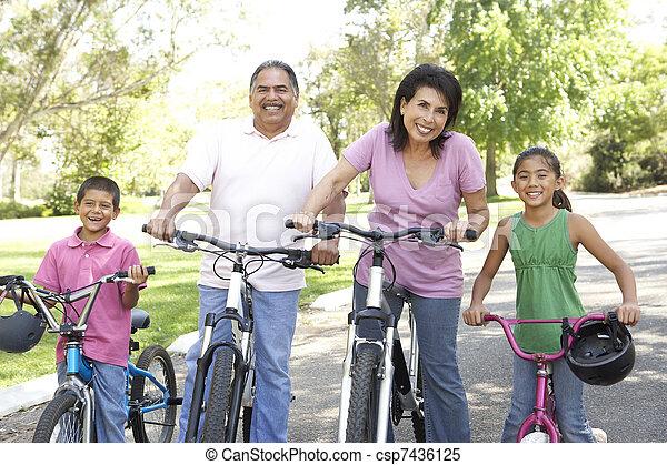 Grandparents In Park With Grandchildren Riding Bikes - csp7436125