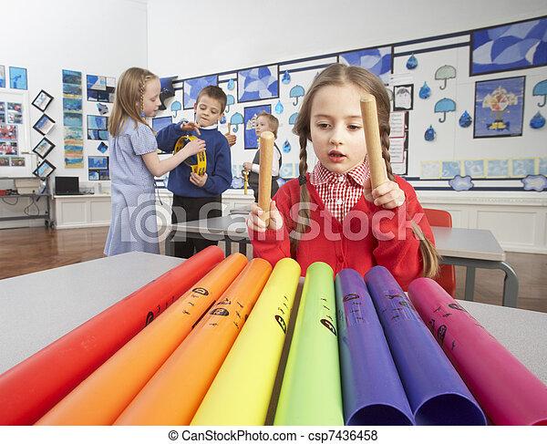 Group Of Primary Schoolchildren Having Music Lesson In Classroom - csp7436458