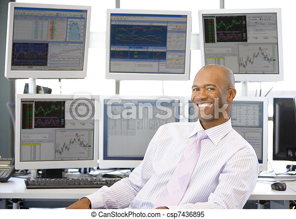 Portrait Of Stock Trader In Front Of Computer Monitors - csp7436895