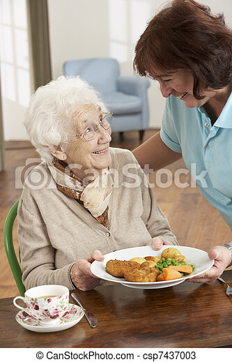 Senior Woman Being Served Meal By Carer - csp7437003