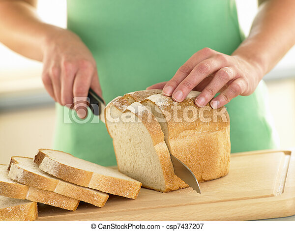 Woman Slicing A Loaf Of White Bread - csp7437207
