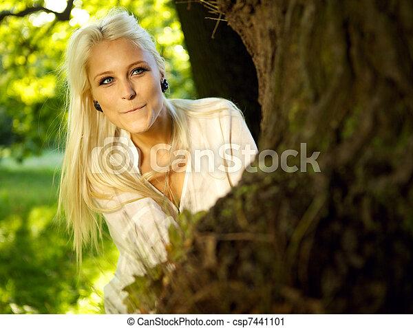 Pretty woman hiding behind tree - csp7441101