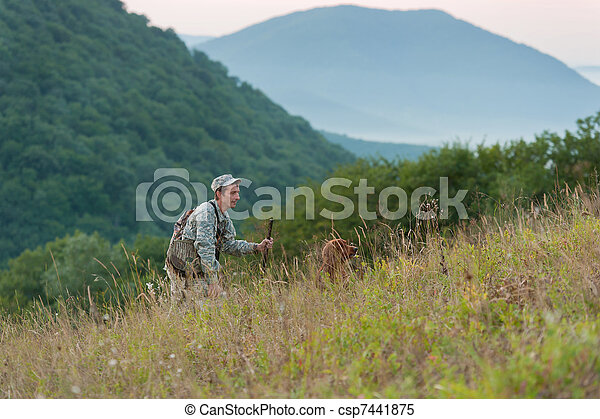 Hunter with dog in countryside - csp7441875
