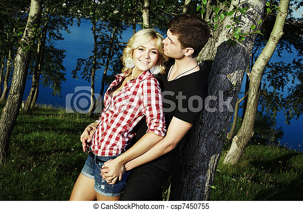 Portrait of love couple embracing outdoor in park - csp7450755