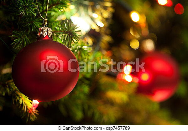 Christmas Ornament with Lighted Tree in Background, Copy Space - csp7457789