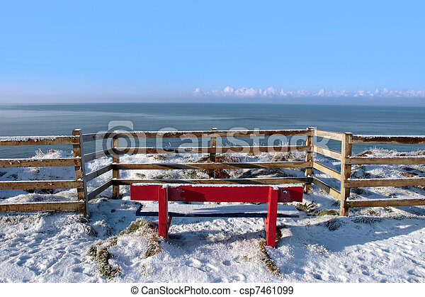 seasonal snow covered red bench sea view - csp7461099