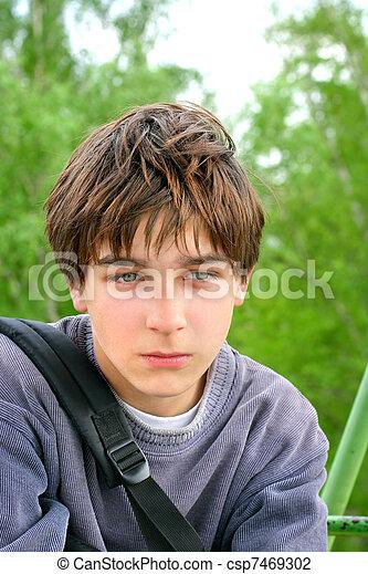 sad teenager sitting on the trees background