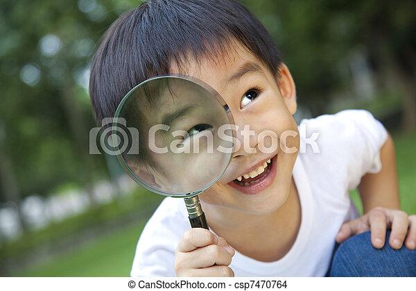 asian boy holding magnifier - csp7470764