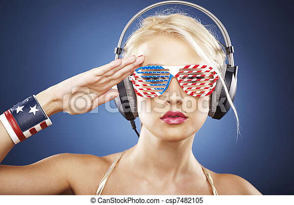 Beautiful blonde model with headphones and American inspired grid glasses dressed in gold swimwear saluting the flag. - csp7482105